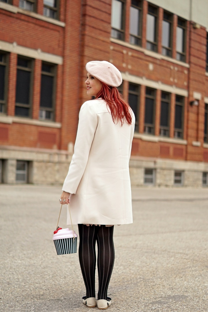 Winnipeg Style Fashion, Loly in the Sky Noela eye lash flats, Kate Spade New York cupcake clutch bag, Anthropologie pink ostrich feather belt, Le chateau beige classic coat, BCBG Jaylin pleated pink skirt