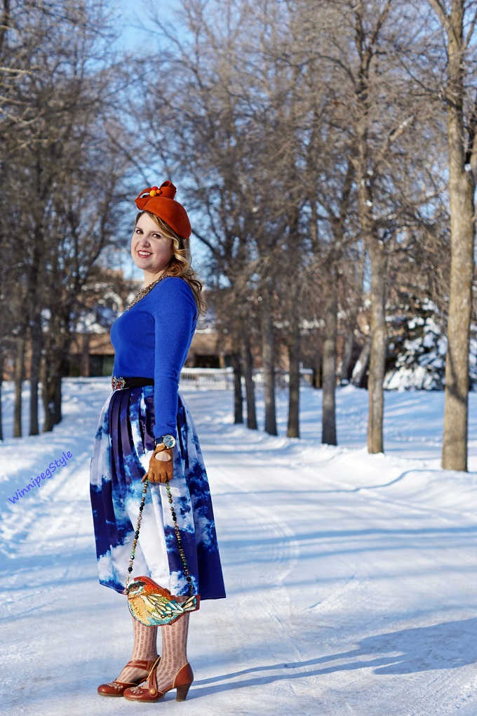 Winnipeg Style, fashion consultant, personal shopper, Coque Millinery by Ericah Rebecca orange wool pom pom winter hat, Chicwish cloud sky print midi skirt, Mary Frances beaded bird clutch purse, Leanimale sloth pin brooch, Lord & Taylor cobalt blue cashmere sweater, orange and blue color combination