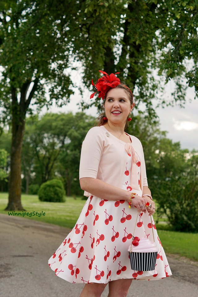WinnipegStyle, Chicwish retro cherry print flare dress, Kate Spade Magnolia Bakery cupcake bag, RW & co blush pink bow tie cardigan, Precis Petite red feather fascinator, Joan River jewelry fruit charm bracelet, John Fluevog LE red pink Fellowship Sandra flats